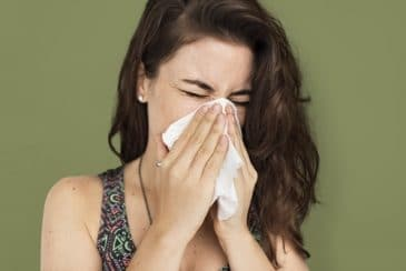 lady sneezing due to allergies